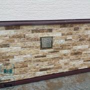 Фото отделки цоколя под камень фиброцементными панелями НИТИХА EJB515. Отливы металлические с покрытием из полиэстера