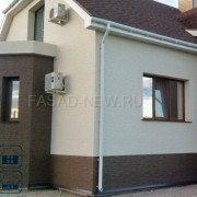 Фото каркасного дома облицованного фасадными фиброцементными панелями NICHIHA под коричневый камень EFX3353 и белую штукатурку 3Д EFX2952
